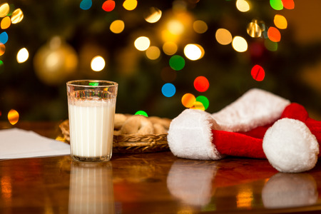 Closeup photo of glass of milk and cookies for Santa on table