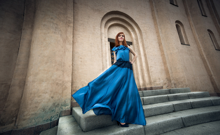 Elegant young woman in fluttering long blue dress walking posing on stone stairs Stock Photo