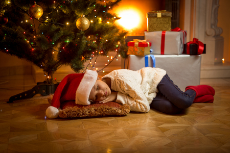 holiday house: Cute girl fell asleep under Christmas tree while waiting for Santa Stock Photo