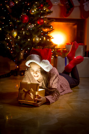 Portrait of cute smiling girl lying on floor at fireplace and looking inside of glowing gift box