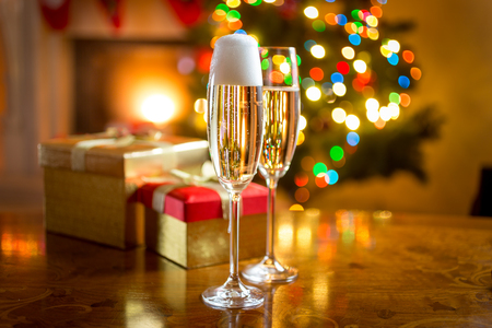 Two champagne glasses on table against fireplace decorated for Christmas Standard-Bild