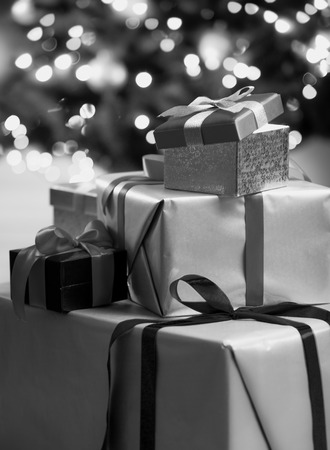 desaturated: Closeup black and white photo of Christmas gift boxes lying on floor at living room Stock Photo