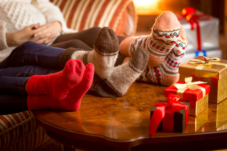 Closeup photo of familys legs in woolen socks next to fireplace at Christmas Stock Photo