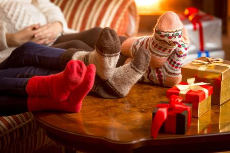 Foto van de benen in wollen sokken familie naast de open haard met Kerstmis close-up
