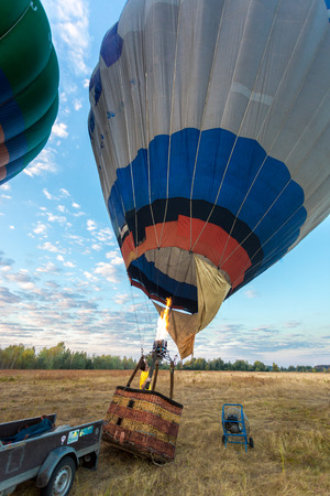 inflation basket: Young pilot filling balloon with hot air from propane heater