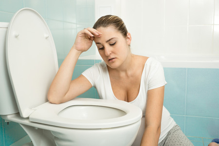 drunk girl: Portrait of young woman feeling sick and leaning on toilet Stock Photo