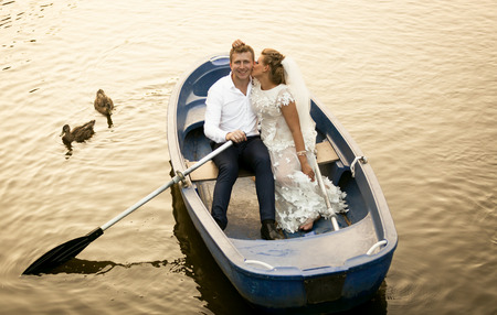 ducks water: Beautiful bride kissing smiling groom while riding on the rowing boat