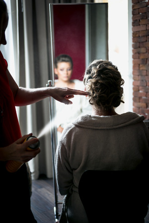 hairspray: Portrait of hairstylist using hairspray on blonde brides hair