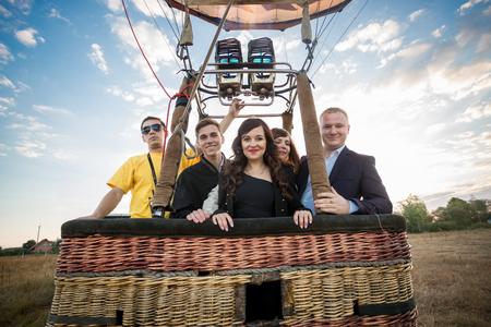 Happy group of people posing in hot air balloon basket