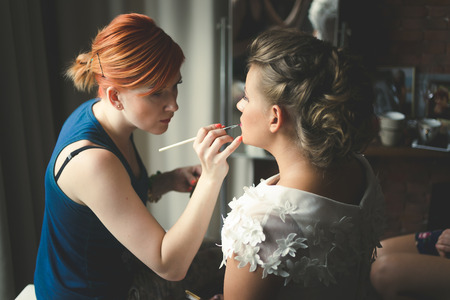 Toned portrait of makeup artist preparing blonde bride at morning Фото со стока