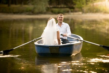 Getinte foto van net getrouwd paar ontspannen en plezier in de roeiboot Stockfoto