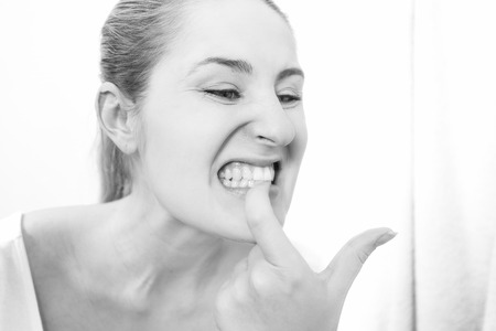 Black and white closeup portrait of young woman looking in mirror and checking teeth Stock Photo