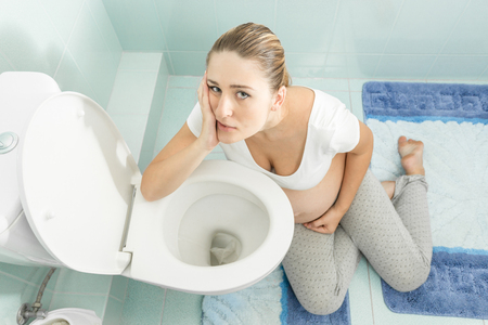 intoxication: Young pregnant woman with intoxication sitting on floor at toilet