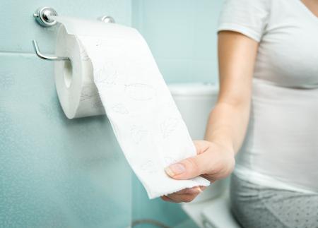 papel de baño: Foto del primer de la mujer sentada en el inodoro y el uso de papel higiénico Foto de archivo