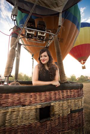 Portrait of beautiful elegant woman posing at hot air balloon basket Фото со стока
