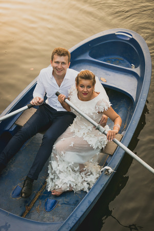 newly married couple: Toned portrait of happy newly married couple riding on rowing boat at sunset Stock Photo