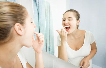 dientes sucios: Retrato de mujer joven recogiendo comida pegada en los dientes con el dedo