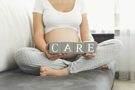 Closeup photo of pregnant woman holding letters making word Care