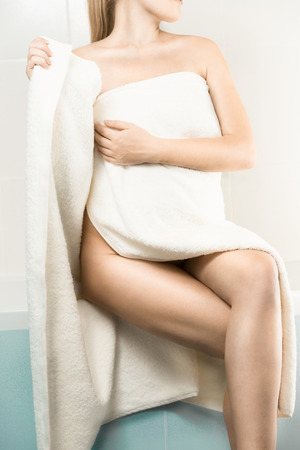 woman in towel: slim woman sitting on side of bath and covering in towel