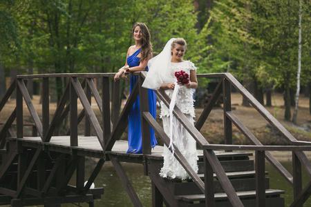 bridesmaid: Beautiful bride and bridesmaid posing on wooden bridge over river