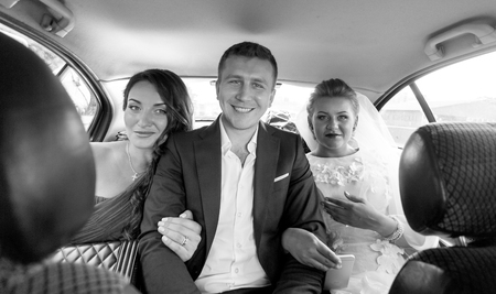 back seat: Black and white portrait of happy smiling groom sitting on back seat with bride and bridesmaid