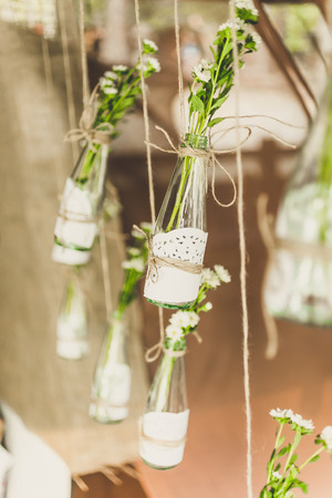 Closeup toned photo of decorated bottles with flowers hanging on twine Standard-Bild