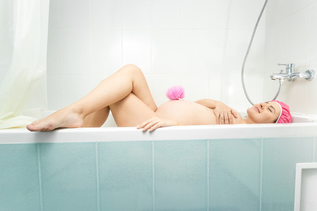 lying in bathtub: Beautiful young pregnant woman lying in bathtub