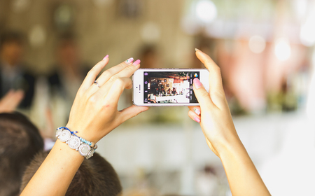 Closeup photo of woman making photo on mobile phone at wedding ceremony Stockfoto