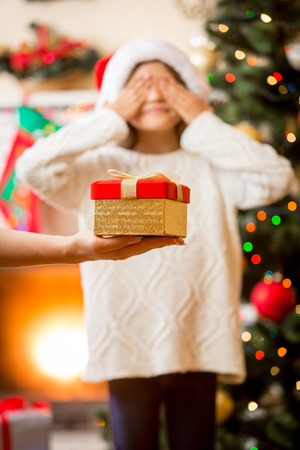 git: Mother holding on hand Christmas gift and giving it to daughter
