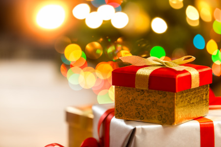christmas tree presents: Closeup photo of Christmas gift boxes on the background of lights