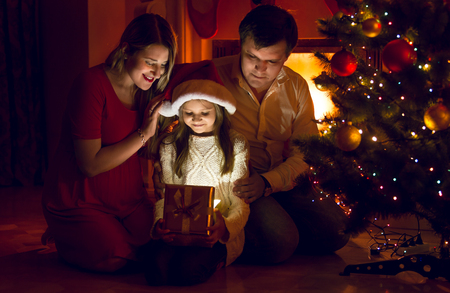 looking inside: Happy parents and cute daughter looking inside of Christmas present