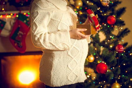 big woman: Toned photo of pregnant woman posing with Christmas gift box Stock Photo