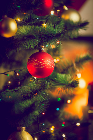 Closeup toned photo of red bauble on Christmas tree next to fireplace at living room