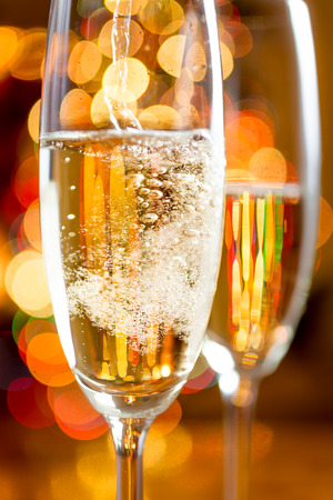 champagne flute: Macro shot of bubbles of Champagne against sparkling lights Stock Photo