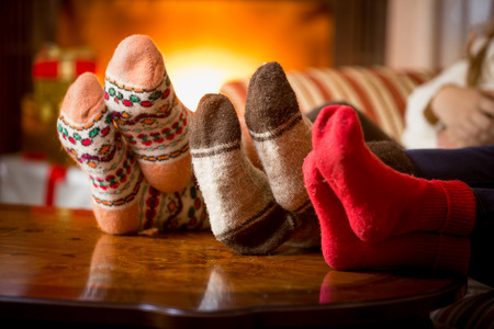 Closeup photo of family feet in wool socks at fireplace Foto de archivo