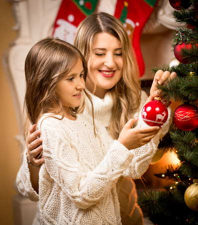 decorate: Portrait of smiling girl helping mother to decorate Christmas tree