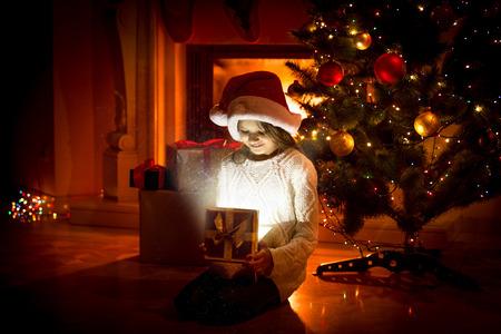 cajas navideñas: Retrato de niña linda sentada en el suelo y que sostiene el actual cuadro