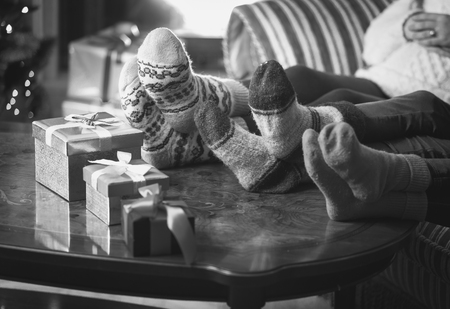 Black and white photo of family warming feet at fireplace