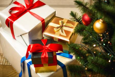 Regali di Natale in scatole colorate sul pavimento a soggiorno Archivio Fotografico