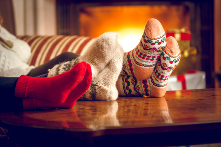 Closeup photo of family warming feet at fireplace