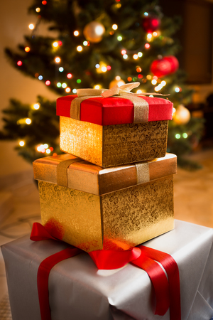 christmas paper: Closeup photo of golden and red gift boxes under Christmas tree Stock Photo