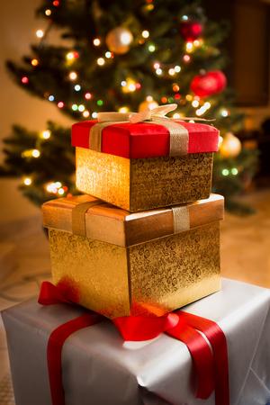cajas navide�as: Foto del primer de cajas de oro y rojas de regalo bajo el �rbol de Navidad