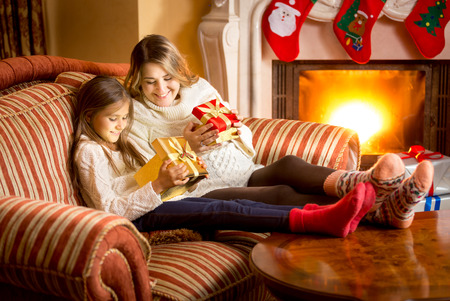 baby open present: Happy mother and daughter looking inside of Christmas gift box Stock Photo
