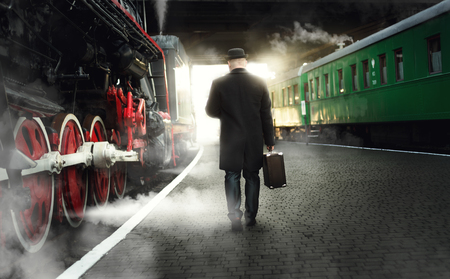 bowler hat: Rear view of man in bowler hat with suitcase walking on the platform next to steaming locomotive