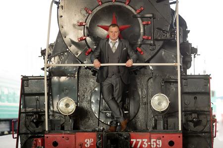 peron: Elegant man posing on old steam locomotive