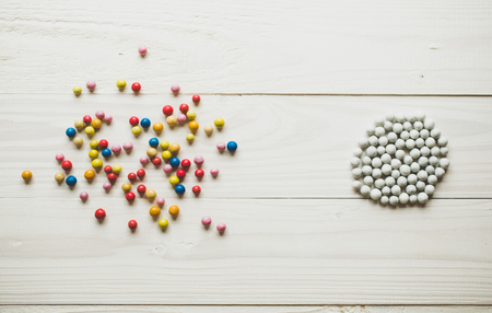 chaos order: Chaotic colorful balls and organized white balls. Concept of order and chaos Stock Photo