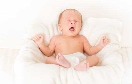 Portrét roztomilý chlapeček ležel v posteli a zívání