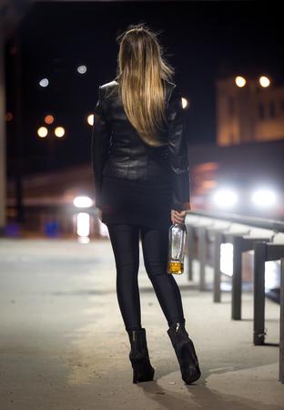 prostituta: Vista trasera de la mujer que presenta en la carretera por la noche