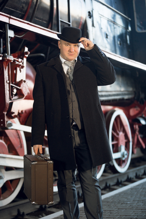 bowler: Portrait of man in retro suit, bowler hat and suitcase posing at old locomotive