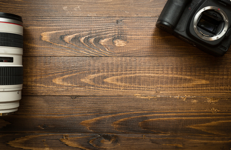 Top view of digital camera and zoom lens on wooden background